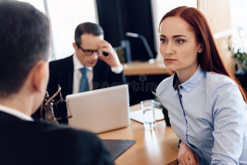 红发美丽的妇女听殷勤地看离婚律师的人 免版税库存照片