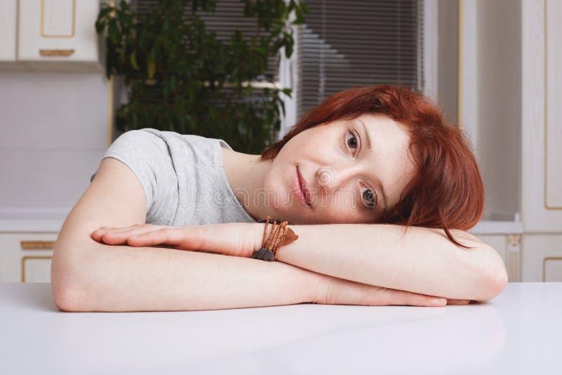 红发美好的女性模型画象倾斜在手,在关于房子的坚苦工作以后被用尽的看起来,穿戴随便,花费 免版税库存照片