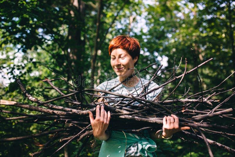 红发行家女孩收集在森林的背景的木柴 库存照片