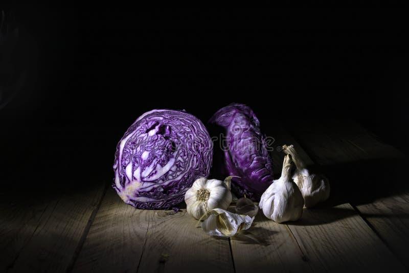 红叶卷心菜一半和成熟大蒜在说谎木表面上的背后照明 在黑背景的静物画 库存照片
