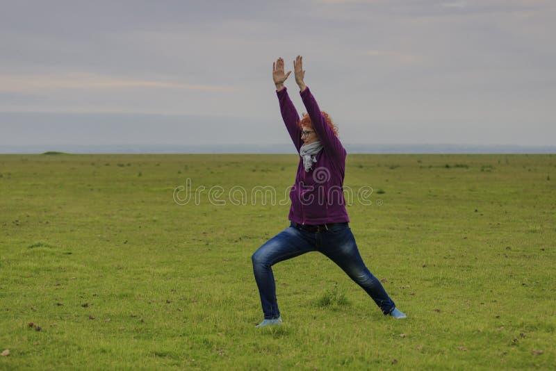 红头发人女子实践的瑜伽战士的位置 免版税库存照片