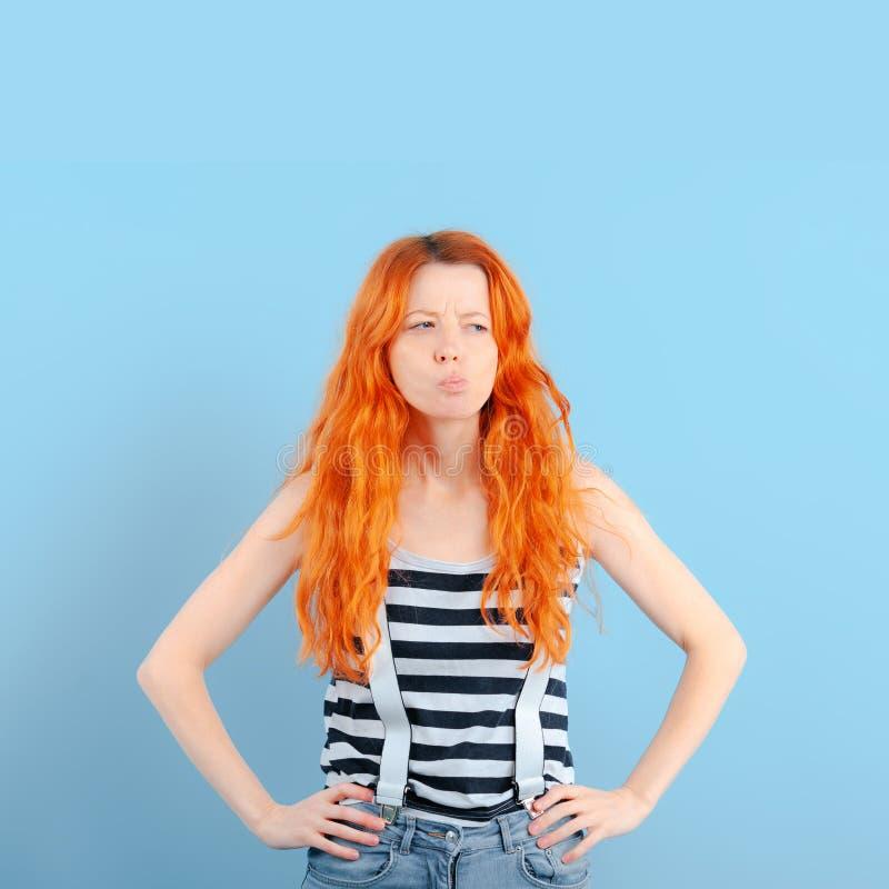 红头发人女孩半眯着的眼睛和皱眉 疑义、选择和怀疑 图库摄影
