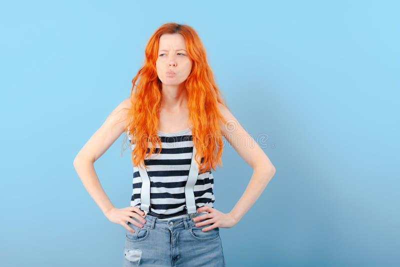 红头发人女孩半眯着的眼睛和皱眉 疑义、选择和怀疑 库存照片