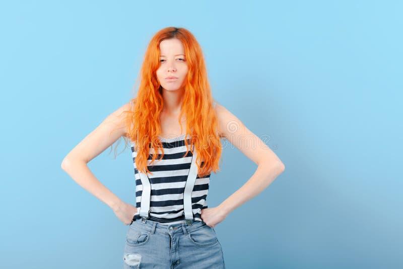 红头发人女孩半眯着的眼睛和皱眉 疑义、选择和怀疑 库存图片