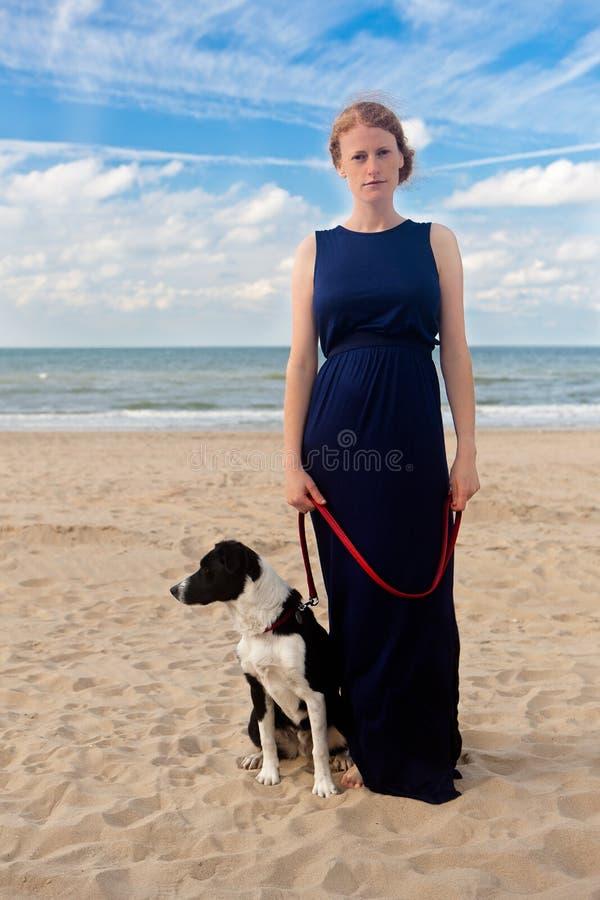 红头发人女孩狗海滩,德帕内,比利时 免版税库存图片