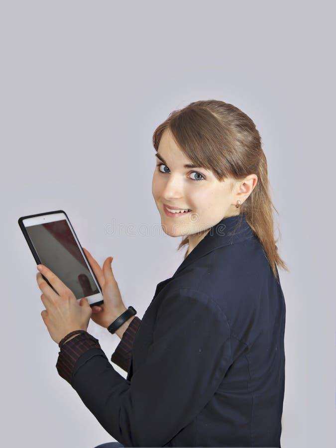 红头发人女小学生拿着有空的黑屏的数字式片剂 隔绝在灰色背景 免版税库存照片