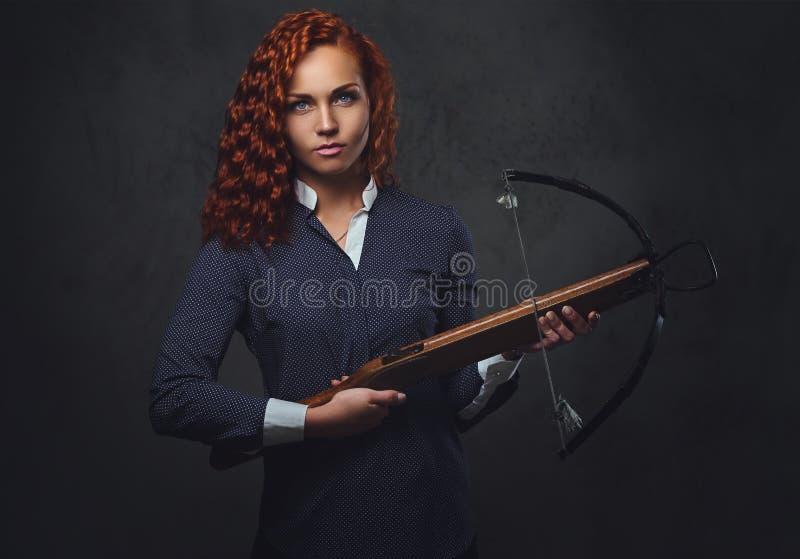 红头发人女性拿着石弓 免版税库存照片