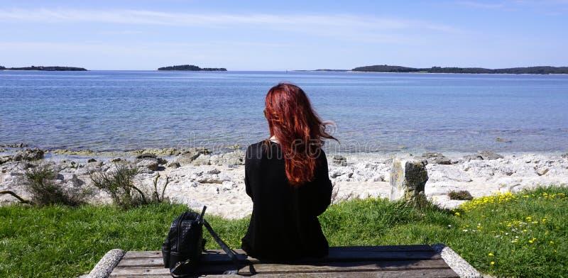红头发人妇女单独坐在海滨前面的长凳 图库摄影