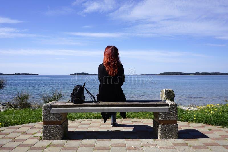 红头发人妇女单独坐在海滨前面的长凳 库存照片