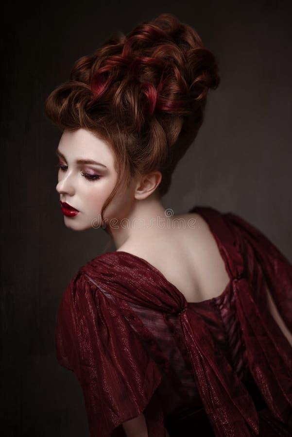 红头发人妇女画象有巴洛克式的发型和平衡的褐红的礼服 免版税库存照片