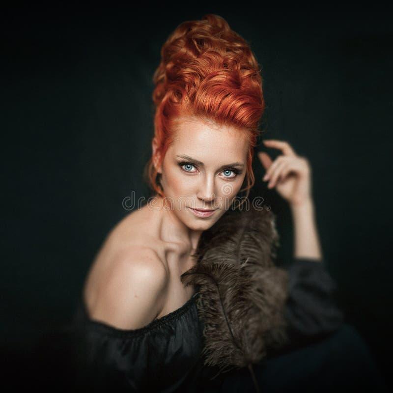 红头发人妇女画象有穿在黑暗的背景的蓝眼睛的黑礼服 女孩doesn ` t神色直接地到照相机里 免版税图库摄影