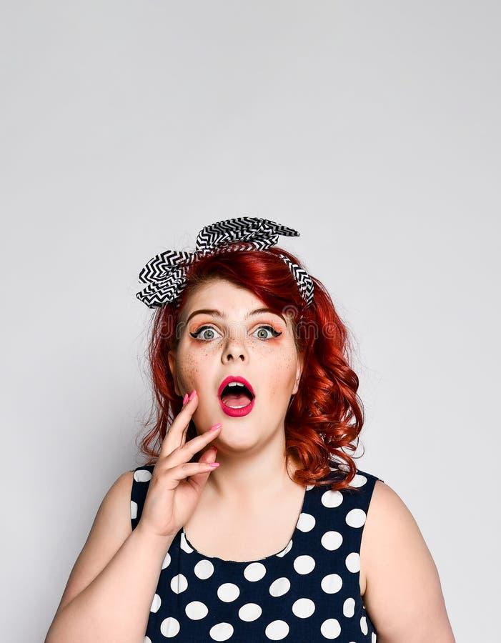 红头发人妇女的Pin 圆点礼服的美丽的减速火箭的女性有红色嘴唇和修指甲钉子和老时尚发型的 库存照片