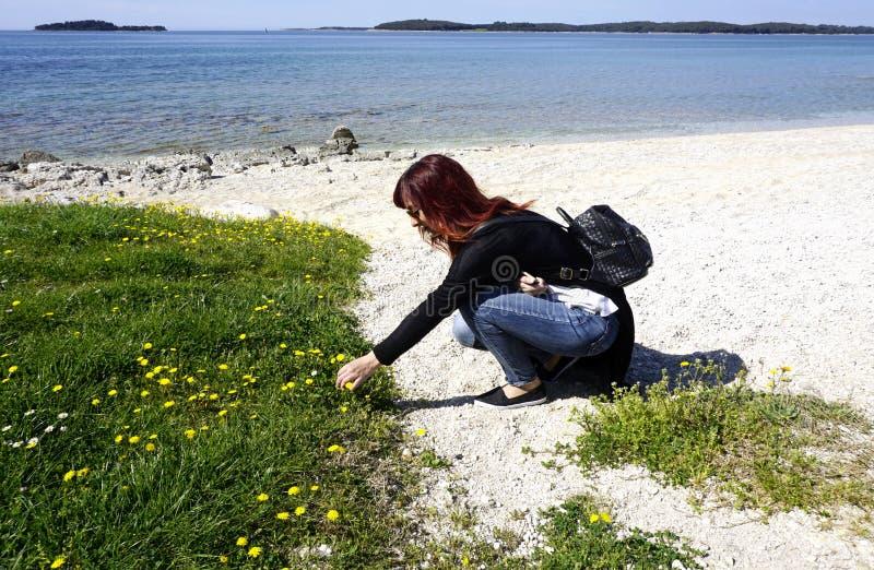 红头发人少妇在沿海附近拾起花 免版税库存图片