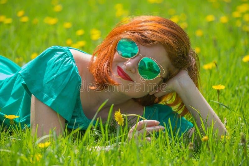 红头发人少妇画象放松在春天公园的 免版税库存照片