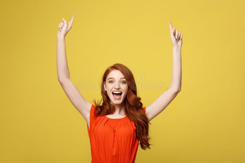 红头发人年轻可爱的妇女画象指向有趣的空间的 隔绝在明亮的黄色 免版税库存照片