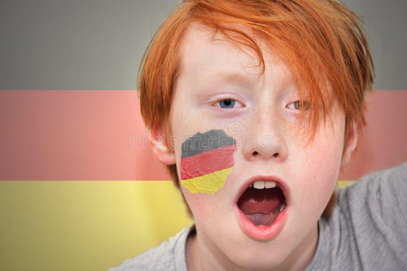 红头发人有在他的面孔绘的德国旗子的爱好者男孩 库存图片