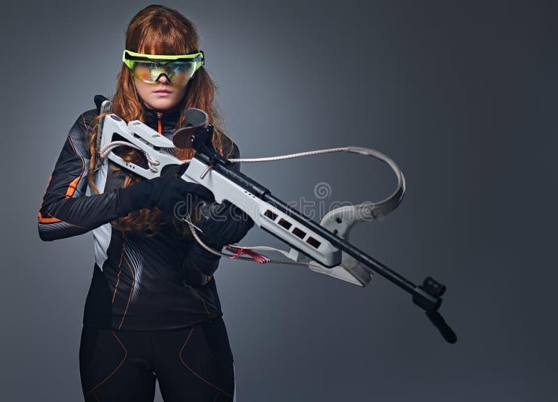 红头发人Biatlon女性运动员举行竞争枪 免版税库存照片
