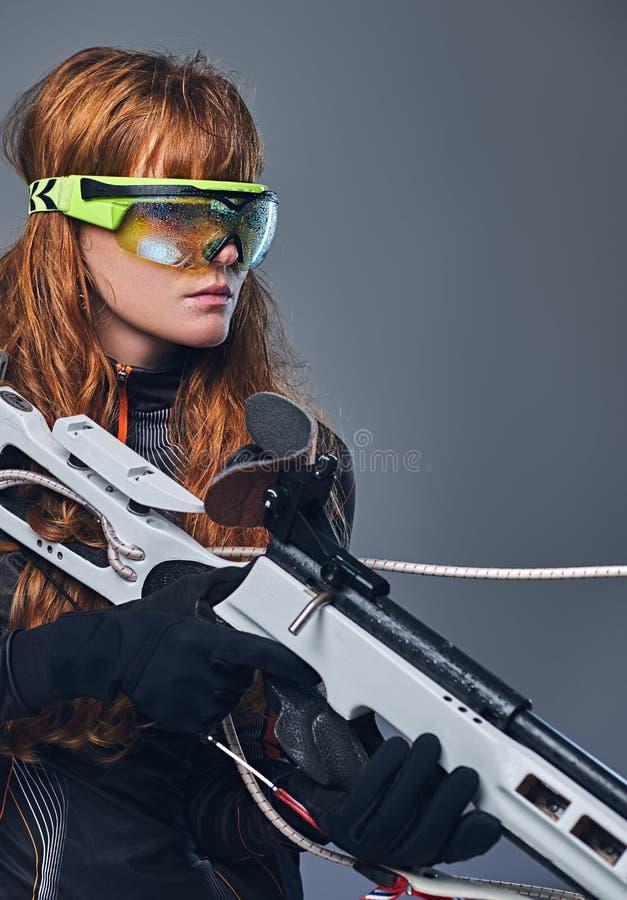 红头发人Biatlon女性运动员举行竞争枪 免版税库存图片