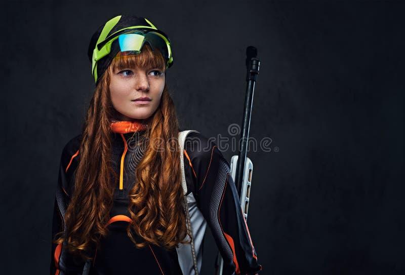 红头发人Biatlon女性运动员举行竞争枪 库存照片