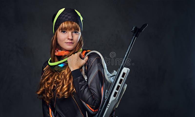 红头发人Biatlon女性运动员举行竞争枪 图库摄影