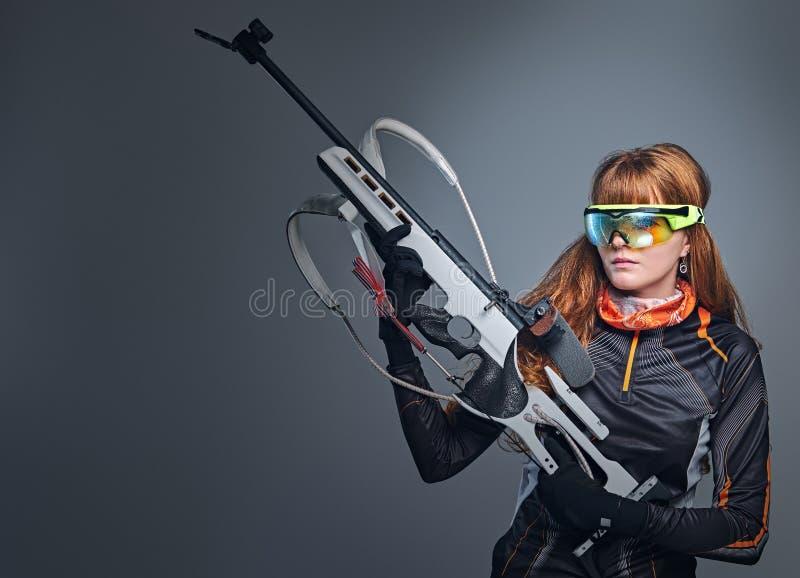 红头发人Biatlon女性运动员拿着竞争枪 免版税库存图片