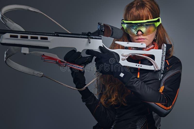 红头发人Biatlon女性运动员拿着竞争枪 库存照片