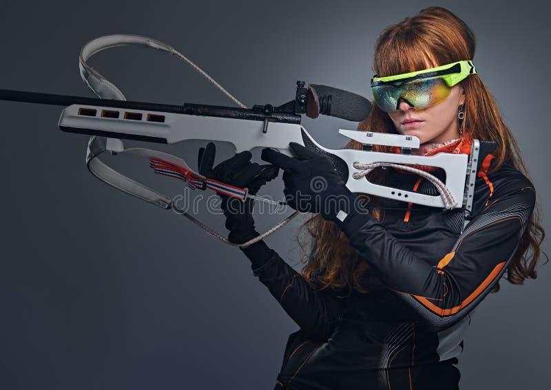 红头发人Biatlon女性运动员拿着竞争枪 库存图片