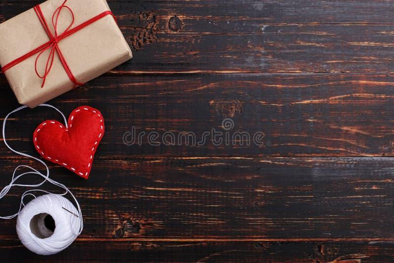 红心做了感觉手工制造,礼物,在螺纹和针旁边,在一张木桌 妇女的天概念,拷贝空间 库存图片