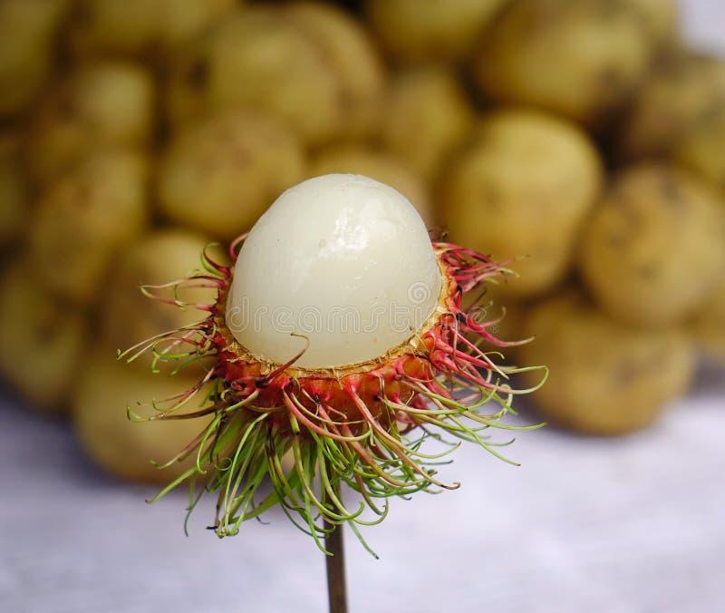 红毛丹果子待售在农村市场上 库存图片