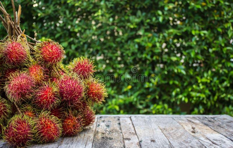 红毛丹,在木地板上的亚洲果子 免版税库存照片