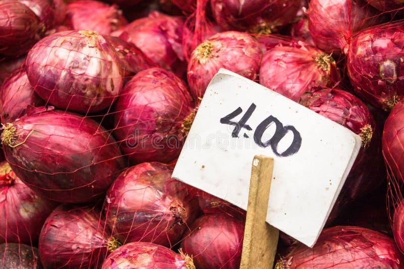 红洋葱新鲜和有机在销售中在菜停留演出地在食物地方市场上与白色价牌 免版税库存图片