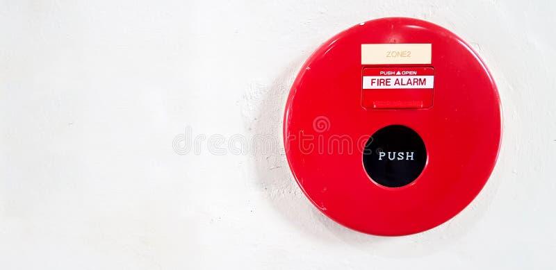 红火警报在白色墙壁上的按钮登上 库存图片
