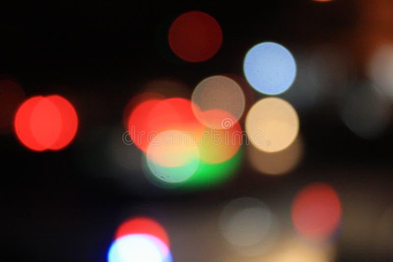 红灯的模糊的照片在与许多的晚上bokeh和圈子和五颜六色的颜色 图库摄影