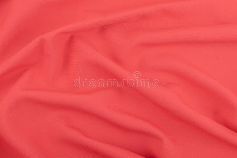红珊瑚暗淡织品的纹理与折叠的 起波纹的红色丝织物特写镜头以玫瑰色形式 库存照片