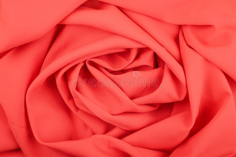 红珊瑚暗淡织品的纹理与折叠的 起波纹的红色丝织物特写镜头以玫瑰色形式 免版税库存照片