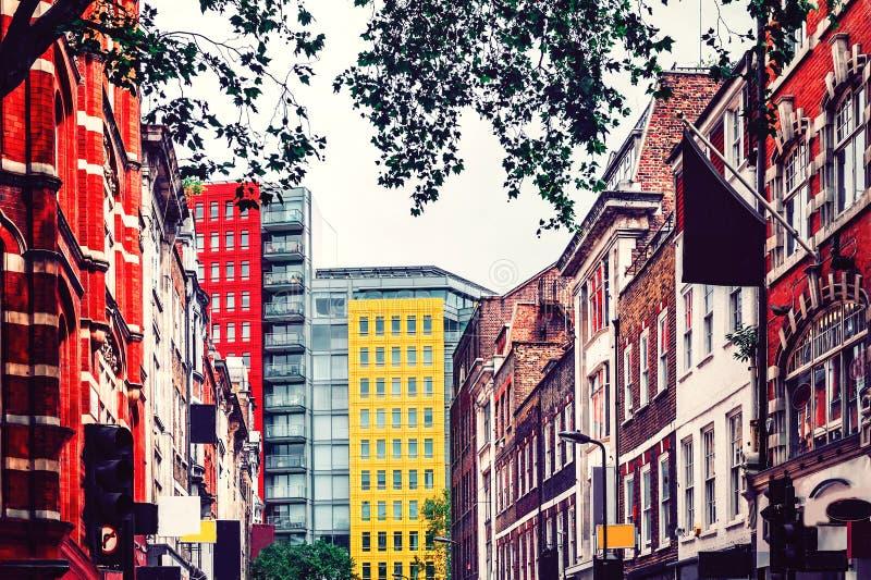 ?? 红砖传统英国房子围拢的黄色高公寓楼 库存照片