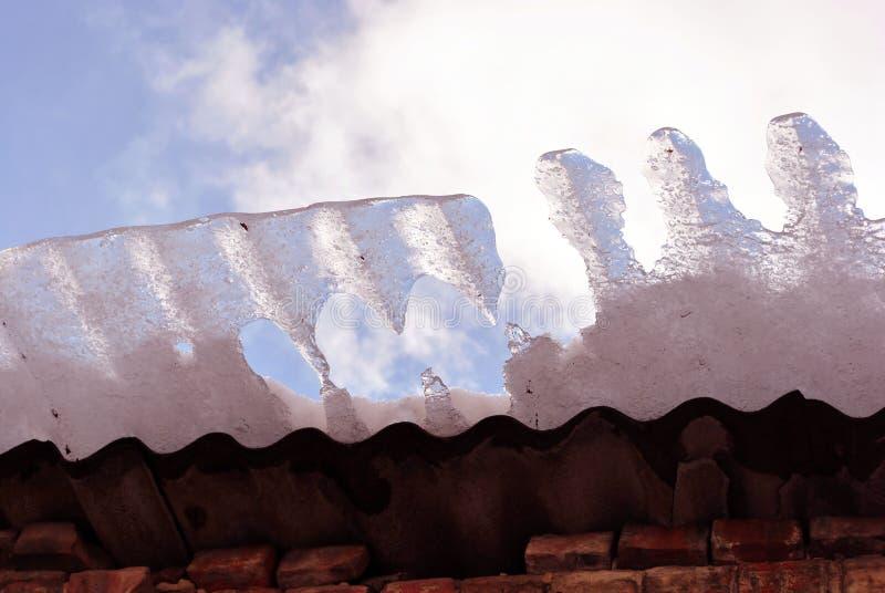红砖墙壁,有落熔化的冰的,从地面的看法屋顶在蓝色多云天空背景关闭  库存图片