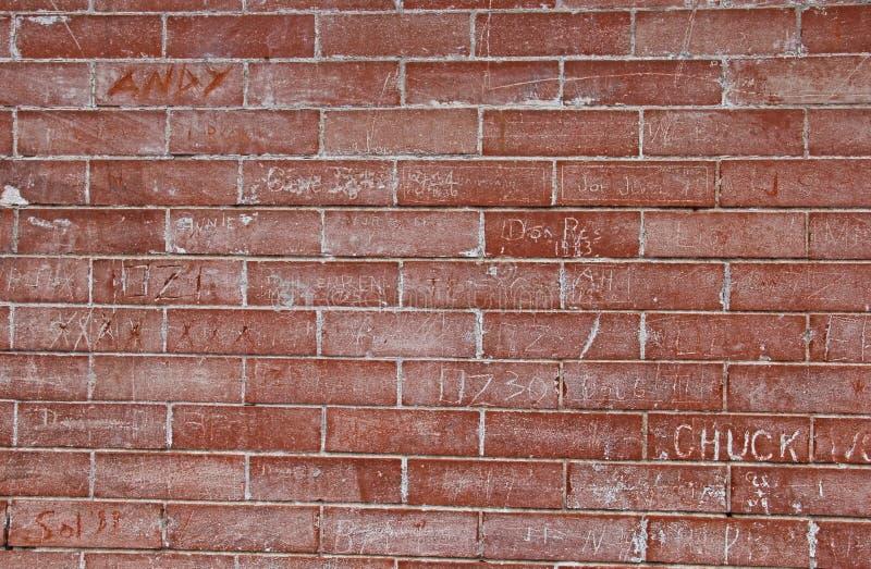 红砖墙壁以街道画抓痕 图库摄影