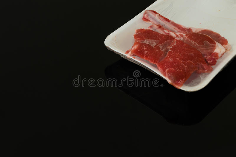 红肉被包装的片断在黑背景的 库存图片