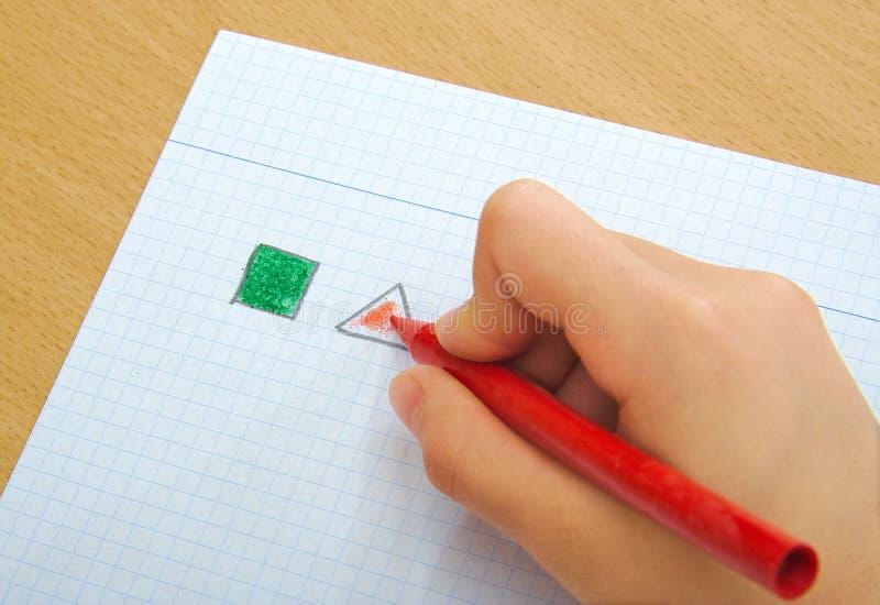 画红色三角和绿色正方形与的孩子 库存图片