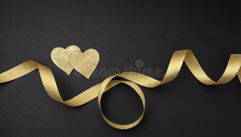 红色上升了 两金黄心脏顶视图与缎带的反对黑背景 库存照片