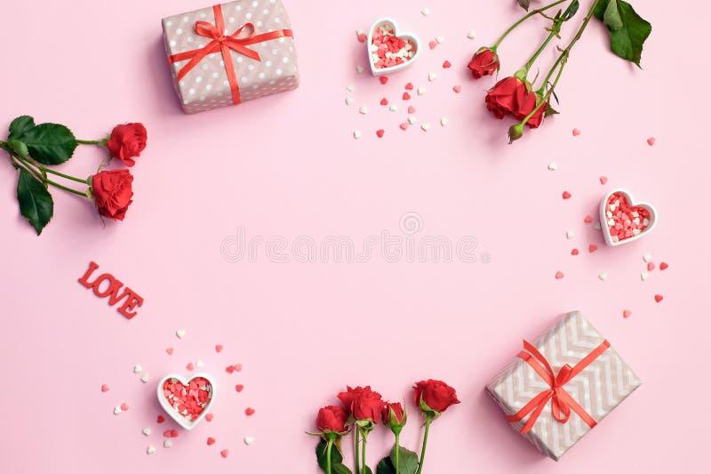 红色上升了 框架由玫瑰色花,在桃红色背景的礼物心脏制成 重点 免版税库存照片