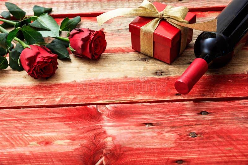 红色上升了 红葡萄酒瓶、玫瑰和一件礼物在木背景 免版税库存图片