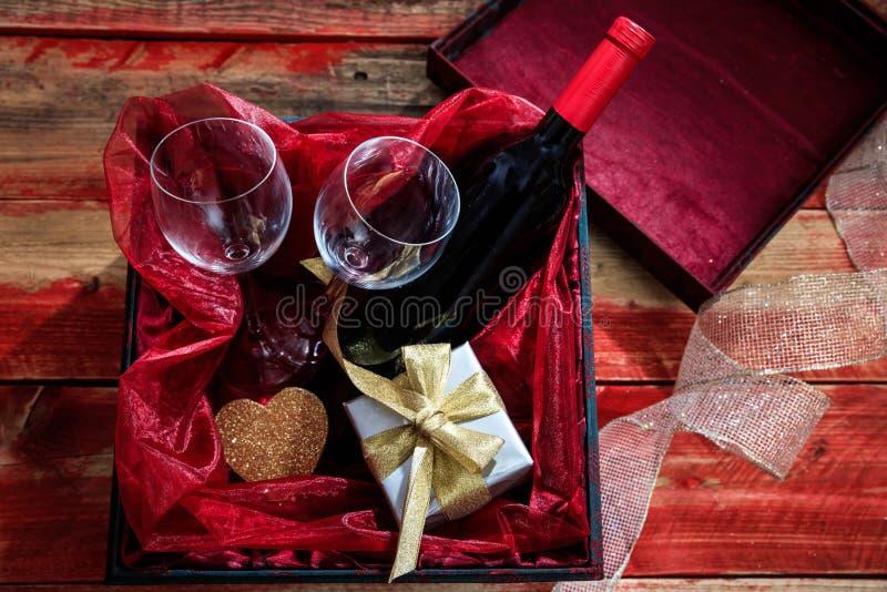 红色上升了 红葡萄酒瓶、玻璃和一件礼物在箱子,木背景 库存图片
