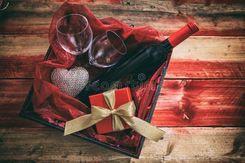 红色上升了 红葡萄酒瓶、玻璃和一件礼物在箱子,木背景 库存照片