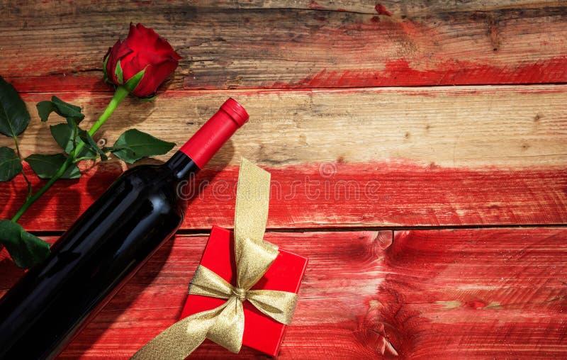 红色上升了 红葡萄酒瓶,玫瑰色和在木背景的一件礼物 免版税库存图片