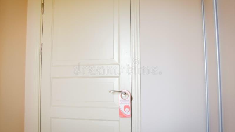红色不干扰垂悬在木门的标志在旅馆 图库摄影