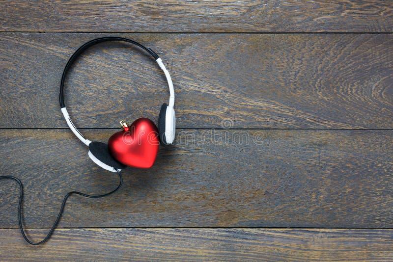 红色与耳机的心脏形状听的音乐在木头 免版税图库摄影