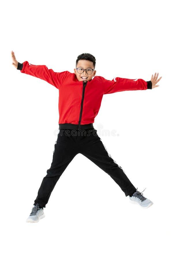 红色体育的亚裔男孩在一个白色背景跳 Portra 免版税库存照片
