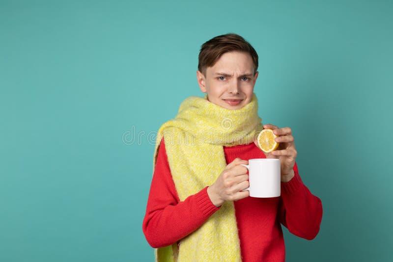 红色做滑稽的面孔的毛线衣和黄色围巾的年轻可爱的人,拿着白色杯子和切的柠檬在手上 库存图片